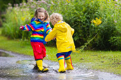 Kids play in rain and puddle in autumn. Little boy and girl play in rainy summer park. Children with colorful rainbow jacket and waterproof boots jump in puddle Royalty Free Stock Image