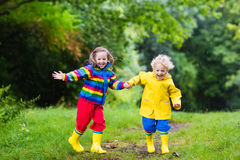 Kids play in rain and puddle in autumn. Little boy and girl play in rainy summer park. Children with colorful rainbow jacket and waterproof boots jump in puddle Stock Photography