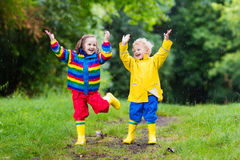 Kids play in rain and puddle in autumn. Little boy and girl play in rainy summer park. Children with colorful rainbow jacket and waterproof boots jump in puddle Royalty Free Stock Photography