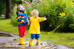 Kids play in rain and puddle in autumn. Little boy and girl play in rainy summer park. Children with colorful rainbow jacket and waterproof boots jump in puddle Royalty Free Stock Photo
