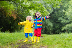Kids play in rain and puddle in autumn Royalty Free Stock Photo