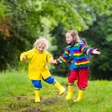 Kids play in rain and puddle in autumn. Little boy and girl play in rainy summer park. Children with colorful rainbow jacket and waterproof boots jump in puddle Stock Image