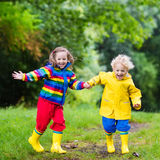 Kids play in rain and puddle in autumn. Little boy and girl play in rainy summer park. Children with colorful rainbow jacket and waterproof boots jump in puddle Stock Images