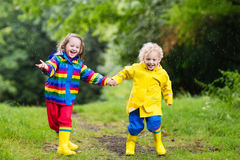 Kids play in rain and puddle in autumn. Little boy and girl play in rainy summer park. Children with colorful rainbow jacket and waterproof boots jump in puddle Stock Photo