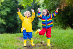 Kids play in rain and puddle in autumn. Little boy and girl play in rainy summer park. Children with colorful rainbow jacket and waterproof boots jump in puddle Royalty Free Stock Images