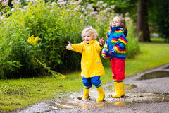 Kids play in rain and puddle in autumn Stock Images