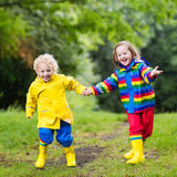 Kids play in rain and puddle in autumn Stock Photos