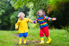 Kids play in rain and puddle in autumn Royalty Free Stock Image