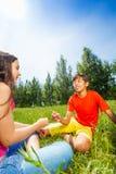 Kids play rock-paper-scissors on grass Stock Photos