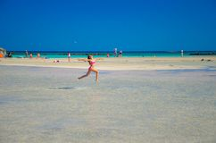 Kids play and run on the famous sandy beach of Elafonissi, Crete, Greece. Kids play and run on the famous sandy beach of Elafonissi, Crete, Greece on June 13 Stock Photos