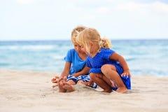 Kids play with sand on summer beach Stock Photos