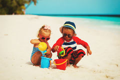 Kids play with sand on summer beach. Little boy and girl play with sand on summer beach Royalty Free Stock Photography