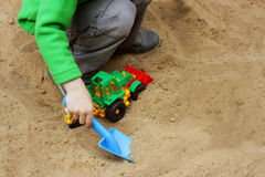 Kids play in the sandbox. Walks for children in the fresh air. Part of the image of a small child who sits in the sandbox and playing with toy construction Stock Photo