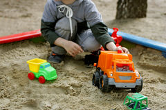 Kids play in the sandbox. Walks for children in the fresh air. Part of the image of a small child who sits in the sandbox and playing with toy construction Stock Image