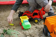 Kids play in the sandbox. Walks for children in the fresh air. Part of the image of a small child who sits in the sandbox and playing with toy construction Stock Photography