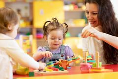 Kids play with shapes and colorful wooden puzzle in a montessori classroom