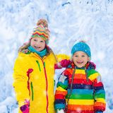 Kids play with snow in winter park Stock Photography