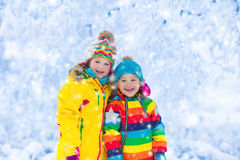 Kids play with snow in winter park Royalty Free Stock Image