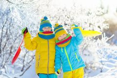 Kids play in snow. Winter sled ride for children. Little girl and boy enjoying sleigh ride. Child sledding. Toddler kid riding a sledge. Children play outdoors stock photography