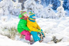Kids play in snow. Winter sled ride for children. Little girl and boy enjoying sleigh ride. Child sledding. Toddler kid riding a sledge. Children play outdoors stock images