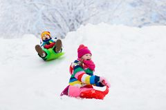Kids play in snow. Winter sled ride for children royalty free stock images