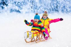 Kids play in snow. Winter sleigh ride for children Stock Images