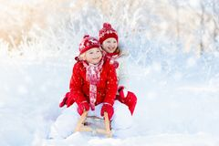 Kids play in snow. Winter sleigh ride for children. Little girl and boy enjoying sleigh ride. Child sledding. Toddler kid riding a sledge. Children play outdoors Stock Photo