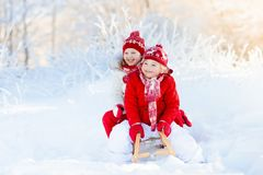 Kids play in snow. Winter sleigh ride for children. Little girl and boy enjoying sleigh ride. Child sledding. Toddler kid riding a sledge. Children play outdoors royalty free stock photography
