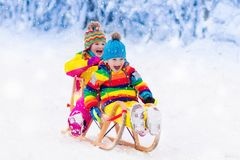 Kids play in snow. Winter sleigh ride for children Royalty Free Stock Photos