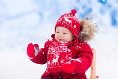 Kids play in snow. Winter sleigh ride for children Royalty Free Stock Image
