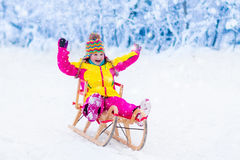 Kids play in snow. Winter sleigh ride for children. Little girl enjoying a sleigh ride. Child sledding. Toddler kid riding a sledge. Children play outdoors in Stock Image