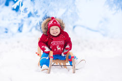 Kids play in snow. Winter sleigh ride for children Royalty Free Stock Images