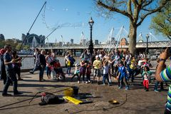 Kids play with soap bubbles during performance of one of the street artists near Jubilee gardens and London Eye Observation Wheel. England Stock Image