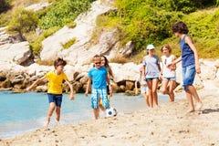 Kids play soccer ball on the sea beach stock photo