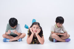 Kids play tablet. Asian kids playing tablet game phone young social girl boy children preoccupied Royalty Free Stock Photo