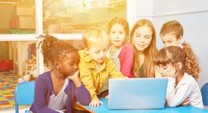 Children at the computer with educator in kindergarten stock photo