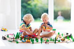 Children play wiht toy train. Kids wooden railway. Kids play with toy train railway. Children playing with wooden trains. Toys for little boy. Two brothers Royalty Free Stock Photo