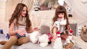 Kids play with toys, older sister is playing with the youngest in the house, the sisters spend time together playing. Soft toys, knitted scarves In the girls stock video