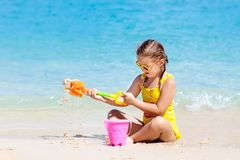 Kids play on tropical beach. Sand and water toy stock images