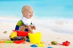 Kids play on tropical beach. Sand and water toy. Child playing on tropical beach. Little girl digging sand at sea shore. Family summer vacation. Kids play with Royalty Free Stock Photo