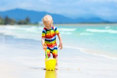Kids play on tropical beach. Sand and water toy. Stock Images