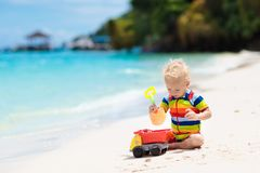 Kids play on tropical beach. Sand and water toy stock photos