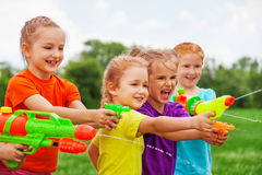 Kids play with water guns on a meadow Royalty Free Stock Image