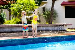 Kids play with water hose at swimming pool. Kids playing with garden hose in backyard with large outdoor swimming pool. Children play with water. Swim wear and Stock Images