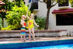 Kids play with water hose at swimming pool. Kids playing with garden hose in backyard with large outdoor swimming pool. Children play with water. Swim wear and Stock Photos