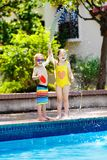 Kids play with water hose at swimming pool. Kids playing with garden hose in backyard with large outdoor swimming pool. Children play with water. Swim wear and Royalty Free Stock Photography