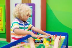 Kids play wooden railroad. Child with toy train. Kids play toy railroad. Little blond curly boy with wooden trains in indoor playground or amusement center royalty free stock images