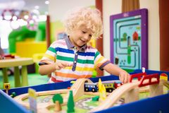 Kids play wooden railroad. Child with toy train. Kids play toy railroad. Little blond curly boy with wooden trains in indoor playground or amusement center royalty free stock photos