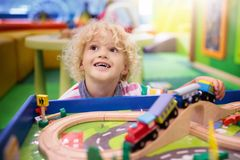Kids play wooden railroad. Child with toy train. Kids play toy railroad. Little blond curly boy with wooden trains in indoor playground or amusement center royalty free stock photo