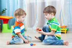 Kids play with wooden toy sitting on the floor Royalty Free Stock Photos